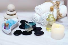 Stellen Sie für Badekurortverfahren auf einer weißen Marmortabelle - aromatisches Öl, Steine für heiße Massage, blaues Badesalz u Stockfoto