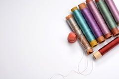 Stellen Sie für das Nähen, die mehrfarbigen Spulen mit Threads, Nadel und Muffe auf weißem Hintergrund ein lizenzfreie stockfotografie
