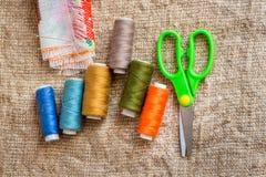 Stellen Sie für das Nähen ein: Scheren, mehrfarbige Threads, Nadeln, Gewebe stockbild