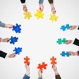 Stellen Sie gemalte Puzzlespielstücke in den Leutehänden auf Grau ein Stockbilder