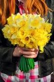 Stellen Sie Mädchen mit Blumenstrauß von Narzissen in seinen Händen dar Lizenzfreie Stockfotos