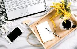 Stellen Sie mit Blumen und einem Bett des Laptops morgens mit Arbeit acces ein Lizenzfreies Stockbild