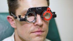 Stellen Sie Nahaufnahme, den Augenarzt gegenüber, der geduldigen Mann mit Optometrikerproberahmen, Sichtprüfungsgerät überprüft m stock footage