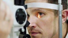 Stellen Sie Nahaufnahme, den Mann gegenüber, der nicht Sehtest mit Kontakt tonometer, cheking Vision, Augeninnendruck an der opti stock footage