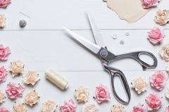 Stellen Sie Scheren mit nähenden Werkzeugen auf weißem Holztisch mit ROS her lizenzfreie abbildung