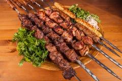 Stellen Sie shashlik ein Kebab mit Gemüse auf Eisenaufsteckspindeln auf hölzernem Hintergrund Lizenzfreie Stockfotografie