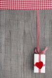 Stellen Sie sich auf einem hölzernen Hintergrund für einen Kupon oder Beleg mit einem roten Herzen dar Stockbilder
