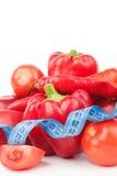 Stellen Sie vom roten grünen Pfeffer, vom glühenden Paprikapfeffer und vom Apfel mit messendem Band ein Stockbild