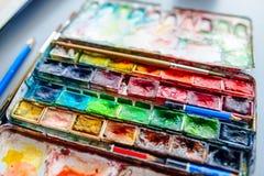Stellen Sie von den Aquarellfarben, -bleistiften und -bürsten in einem Zinnkasten ein lizenzfreie stockbilder
