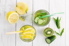 Stellen Sie von den Diätgetränken, Mineralwasser in einer Glas-, frischen grünen Kiwi, in einer Minze und in einer Gurke, in eine stockfotos