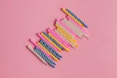 Stellen Sie von den farbigen Geburtstagskerzen ein, die auf rosa Hintergrund lokalisiert werden stockbilder