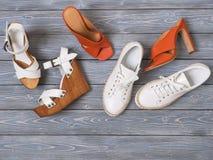 Stellen Sie von den flachen Sandalen der Schuhe der Frauen auf hölzernem Hintergrund ein Frühjahr-Sommer Kollektion Flache Lage A lizenzfreie stockfotografie