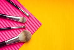 Stellen Sie von den Make-upbürsten gegen Mehrfarbenhintergrund ein Spitzenstandpunkt, flache Lage lizenzfreie stockbilder