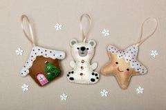 Stellen Sie von den Weihnachtsbaumdekorationen, Haus, Eisbär, Stern, handgemachter Filz auf einem beige Hintergrund mit Schneeflo stockbilder