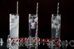 Stellen Sie von drei ein Collins-Glas mit Cocktails ein und färbte Strohe Stockbilder