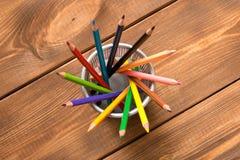 Stellen Sie von farbigen Bleistiften in einem Metallglas auf einem Holztisch ein Beschneidungspfad eingeschlossen lizenzfreies stockfoto