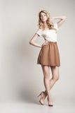 Stellende blonde vrouw met lang krullend haar op wit Stock Foto's