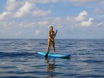 Stellung der jungen Frau auf paddleboard auf Oberfläche Paddleboarding Sporttätigkeit Fastfood- Paddel Mädchen, das sonnigen Tag  stockfotos