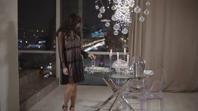 Stellung der jungen Frau nahe Fenster mit einer großartigen Ansicht einer Nachtstadt stock video