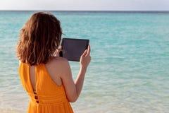 Stellung der jungen Frau vor dem Meer und Anwendung ihrer Tablette während des Sonnenuntergangs lizenzfreie stockfotos