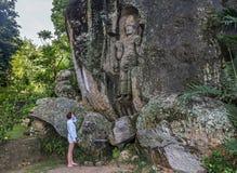 Stellung der jungen Frau vor der enormen schönen alten Statue geschnitzt im Felsen stockfoto