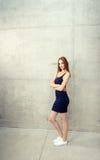 Stellung der jungen Frau - Wand lizenzfreie stockfotos