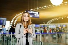 Stellung des jungen Mädchens an Flughafenwartehalle und Plaudern durch Smartphone stockfotos