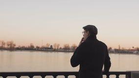 Stellung des jungen Mannes auf dem Damm des Flusses, nahe bei dem Schiff raucht eine Zigarette stock video
