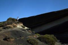 Stellung des jungen Mannes auf einem Berg und einem Aufgeben lizenzfreies stockfoto