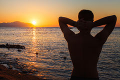 Stellung des jungen Mannes, schöne bunte Sonnenaufgangseelandschaft genießend Lizenzfreies Stockfoto