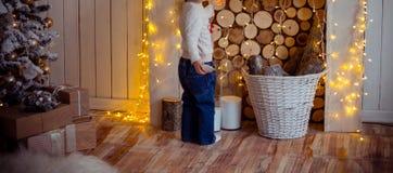 Stellung des kleinen Mädchens nahe dem Weihnachtsbaum, neues Jahr geschenke lizenzfreie stockfotos
