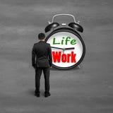 Stellung in Richtung zum Wecker mit Leben- und Arbeitsgesicht Stockfoto