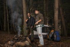 Stellung um die Lagerfeuerbratwürstchen Stockfotos