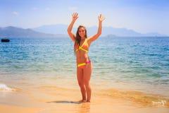 stelt het blonde slanke meisje in bikini boven handen op strand Stock Foto's