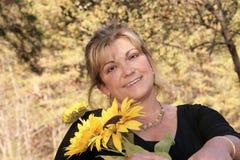 Stelt in openlucht met de zonnebloemen van een glimlachholding stock foto's