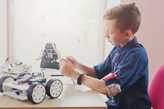 Stem education. Boy creating robot at lab. Stem education. Concentrated boy creating robot at lab. Early development, diy, innovation, modern technology concept royalty free stock photo