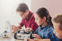 Stem education. Kids creating robots at school. Children creating robots at school, stem education, copy space. Early development, diy, innovation, modern Royalty Free Stock Photos
