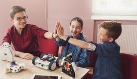 Stem education. Kids creating robots, success. Successful teamwork. Children giving group high-five after creating robots at school, stem education. Early stock image