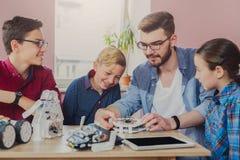 Stem education. Kids creating robots with teacher. Early development, diy, innovation, modern technology concept Stock Photos