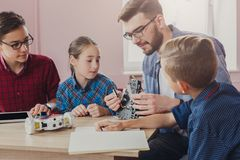 Stem education. Kids creating robots with teacher. Early development, diy, innovation, modern technology concept royalty free stock image