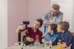 Stem education. Chemical experiment in laboratory. Stem education. Teenagers with teacher making chemical experiment in laboratory with reagents and microscope Royalty Free Stock Photography