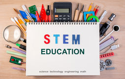 STEM education text on notebook over school supplies or office s. Upplies on school table. Background with school or office material with copy space for text Stock Images