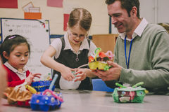 STEM Project In School. Primary school teacher is helping two of his students with a STEM project. They are building something using recycled items and crafts Royalty Free Stock Photo