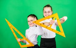 STEM school disciplines. small girls back to school. math lesson. Education and knowledge. Pupil cute girls with big. Rulers. School students learning geometry royalty free stock images