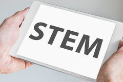 STEM & x28;science, technology, engineering, math& x29; concept with text being displayed on modern touch screen of a white tablet.  Royalty Free Stock Photos