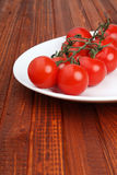 Stem of tomatoes on white plate on wooden background Royalty Free Stock Photo