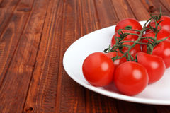 Stem of tomatoes on white plate on wooden background Stock Photo