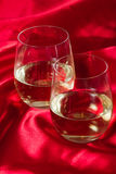 Stemless white wine glasses. Two stemless white wine glasses served on a red silk table cloth royalty free stock photo
