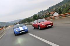 Stemmende auto's die onderaan de weg rennen stock foto's