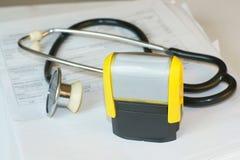 Stempel auf Dokumenten und Stethoskop Stockfotos